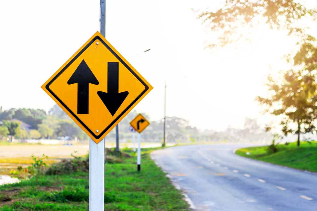 Two traffic signs on the side of the street