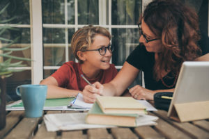 Mother works with son on remote schooling