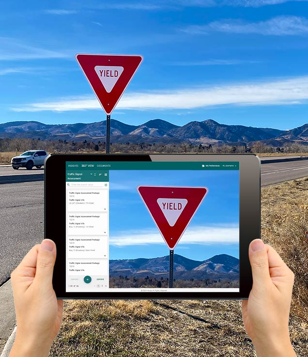 Picture of a rural yield sign being taken on a tablet with mountains in the background.