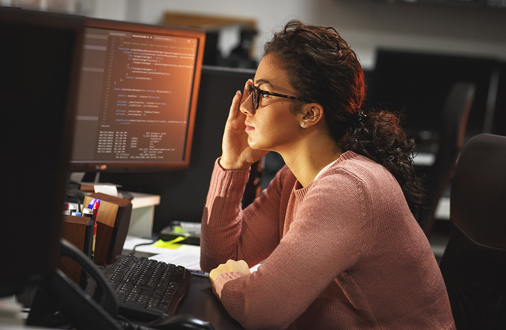 Data analyst reviewing code at her desk.