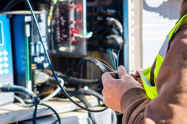 Technician working with wires in a traffic signal box.