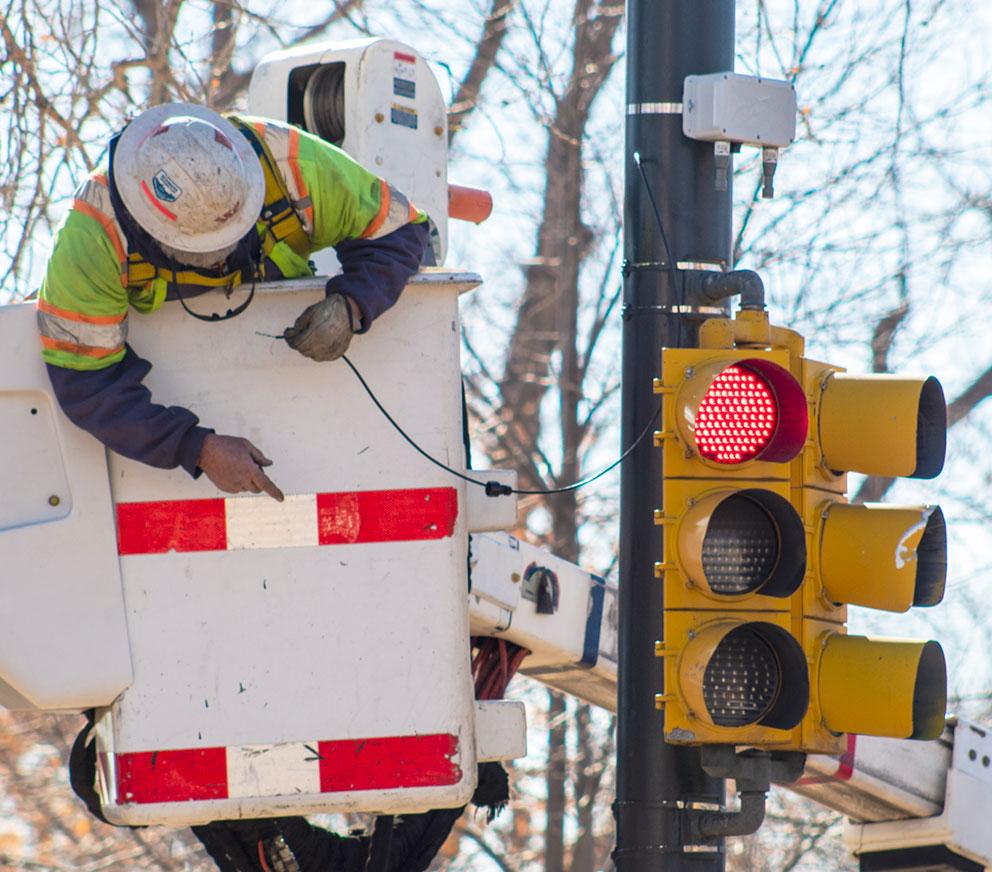 Technician installing Bluetooth device above traffic signal.