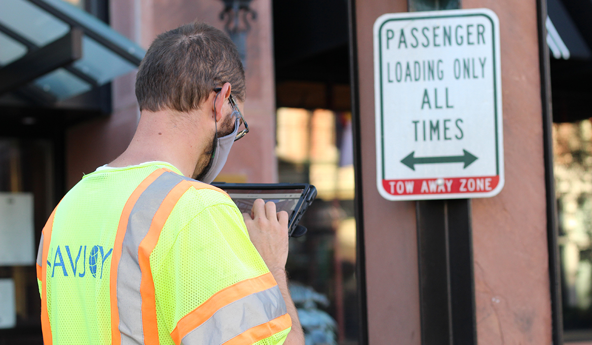 Field technician using Navjoy's software to collect data about a traffic sign.