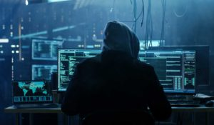 Hooded hacker sitting at a computer