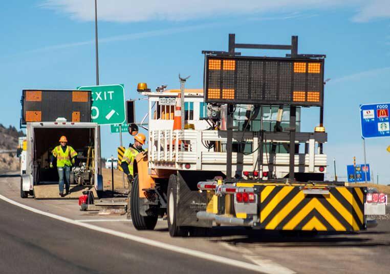 Workers prepare a shoulder closure in a road work zone.